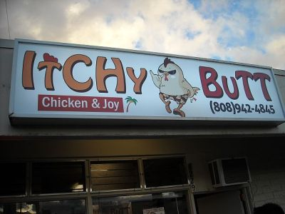 "Notice the chicken on the sign is scratching his rear while giving the ""shaka"" (hang loose) symbol."