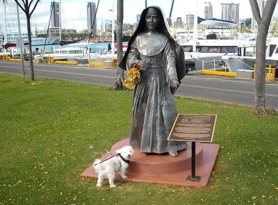 "Our favorite Fluff Pup visits the statue of Marianne Cope. Btw, the giant yacht in the upper left corner is Larry Ellison's ""Musashi""."