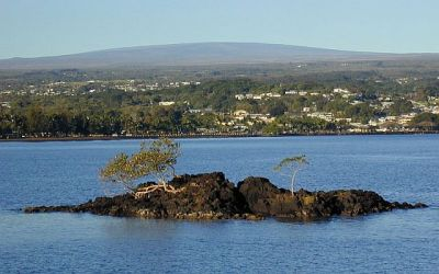 Photo: Mauna Loa looms above the city of Hilo and Hilo Bay. This view is from Mokuola, commonly called Coconut Island. Mokuola and the rock in bottom of photograph formed from a lava flow erupted by Mauna Loa about 1,400 years ago. A flow from Mauna Loa entered what is now Hilo in 1881, and another neared the city in 1984. (S.R. Brantley, USGS)